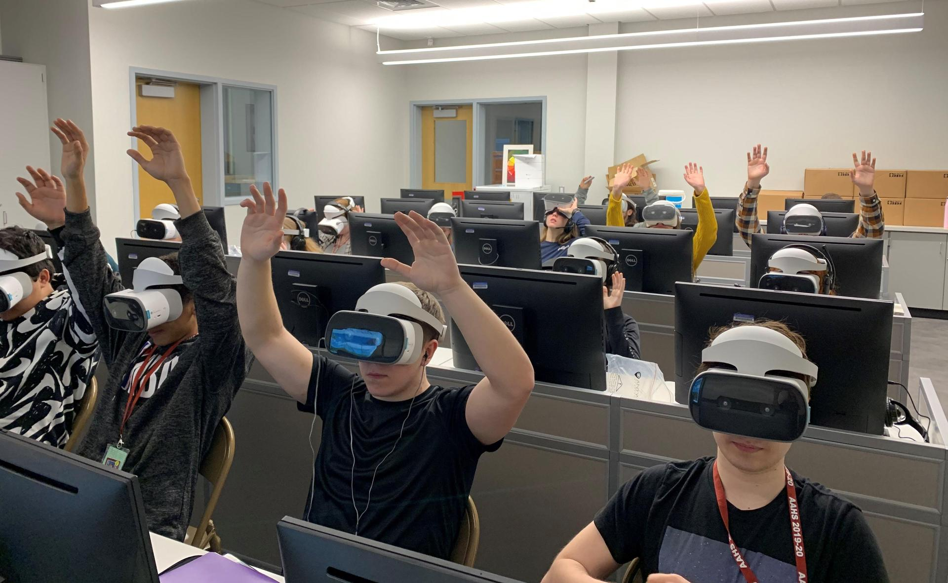 Students from Mr. Borst's physics class ride and analyze VR roller coasters with guest Saint Francis Professor, Dr. Joel Bandstra at the AAHS Library.
