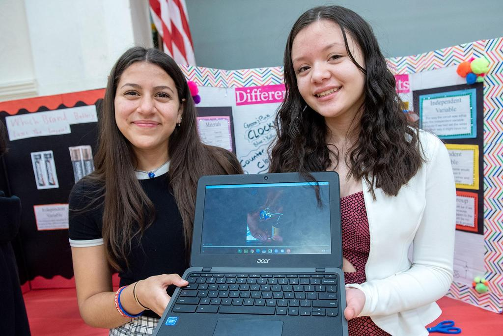Two students hold up a laptop computer in front of their project
