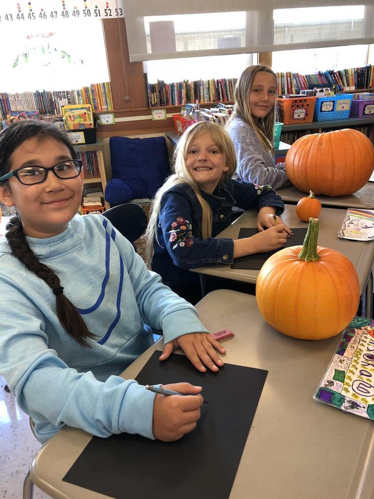 Three girls sketching pumpkins