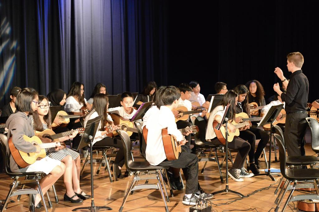 CCA students playing guitar on stage.