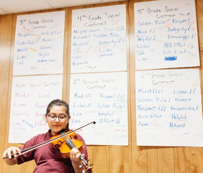 Photo playing violin in front of wall of social contracts.