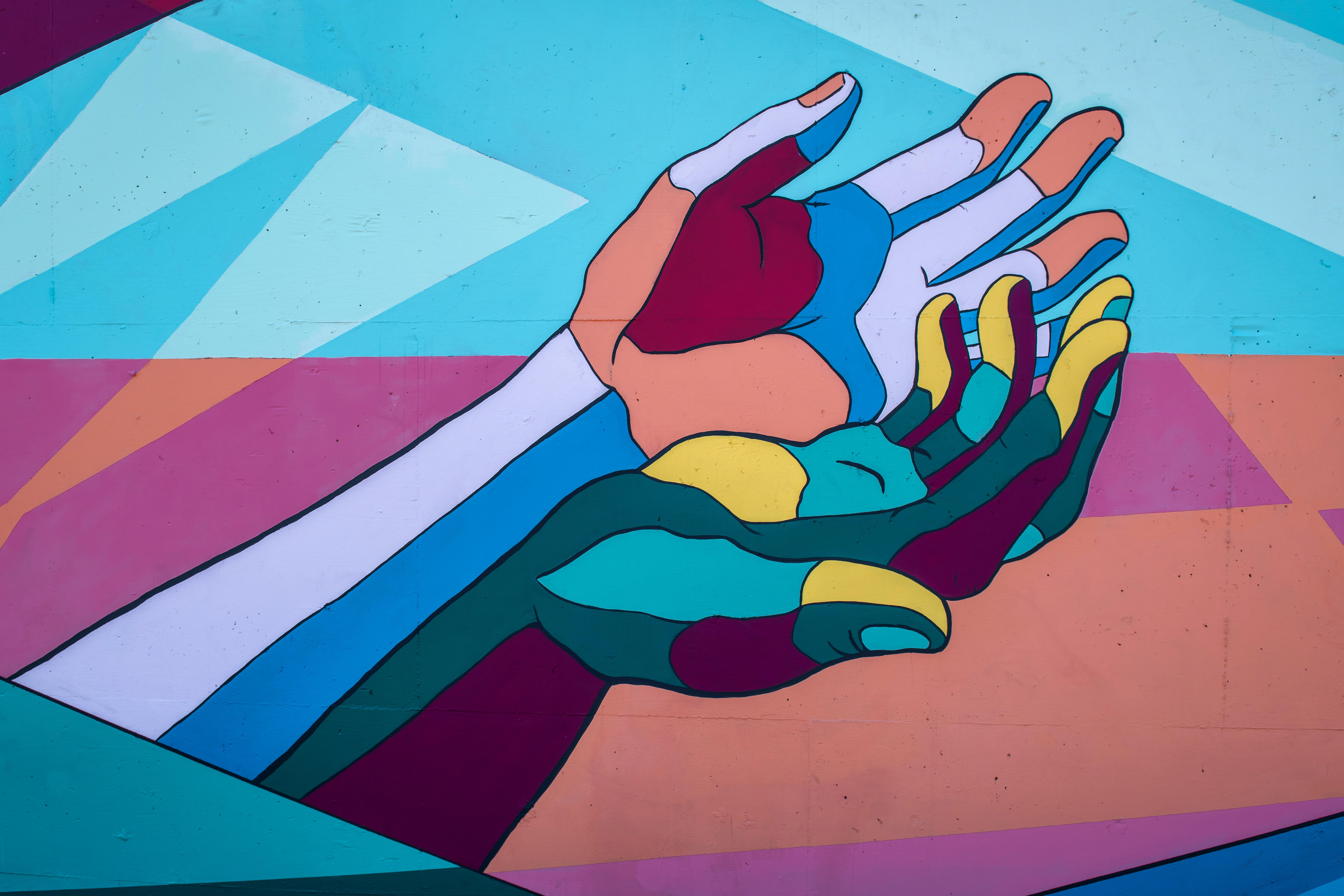 a colorful mural showing two hands supporting each other