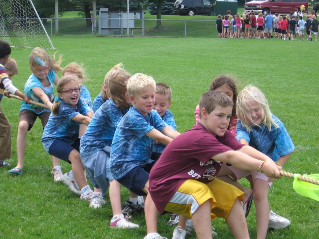 students play tug of war outside in tie dye shirts