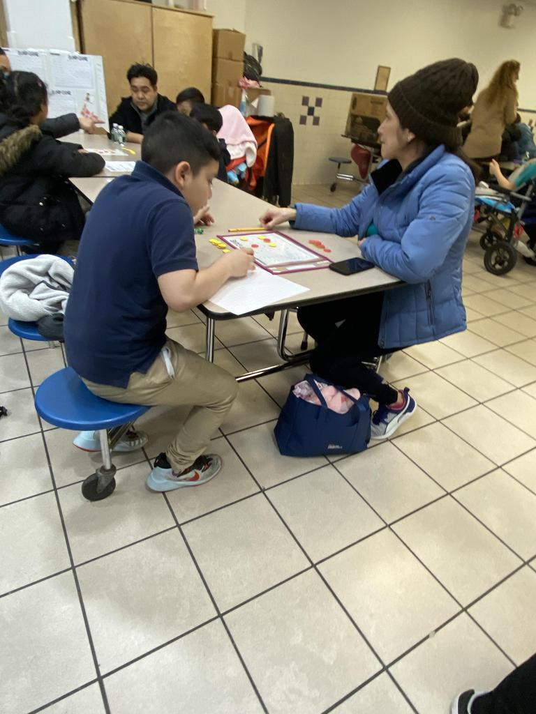 a boy and his mom working on the the math problem together
