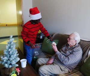 A Page student gives an ornament to a Carveth Village resident after singing Christmas songs.