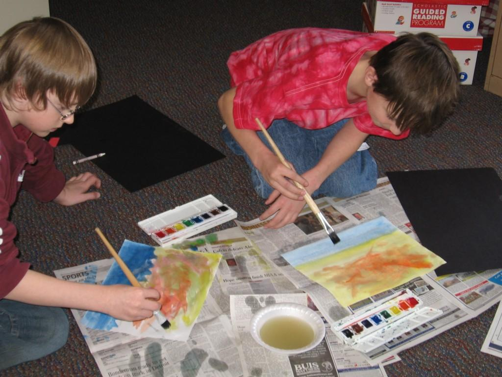 students create art on the floor with water paints