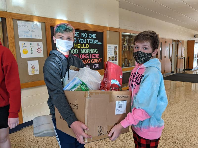 Two boys carry a box of donations