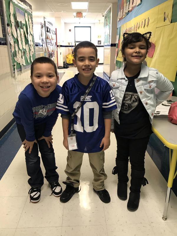 three kids in the hallway wearing their jerseys