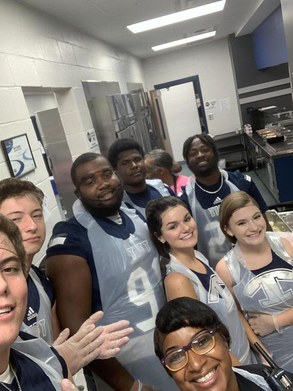 High School Football Players and Cheerleaders Serve Lunch at NEMS Featured Photo