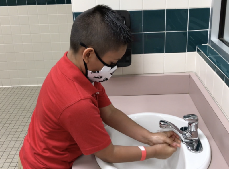 Student washes hands.
