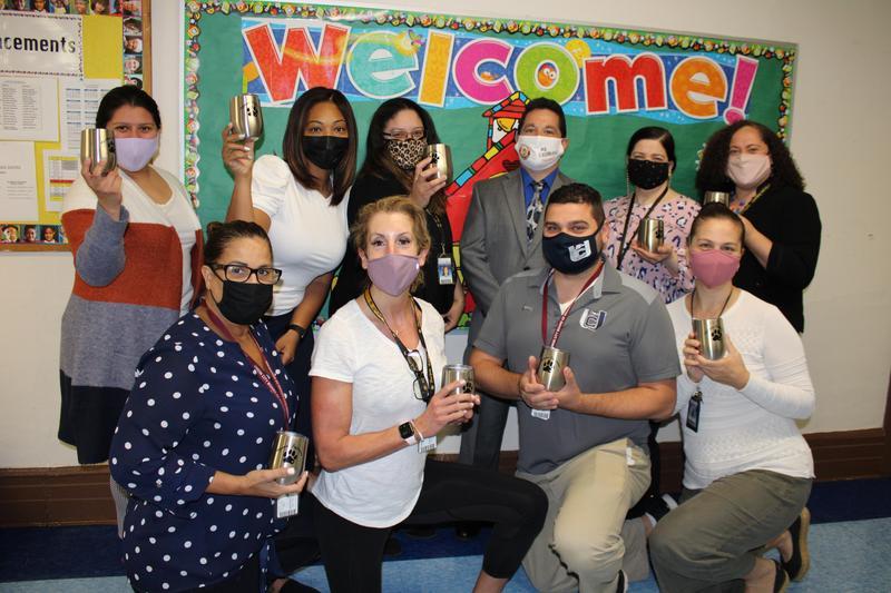 10 teachers posing with Jefferson Jaguar cups in hallway
