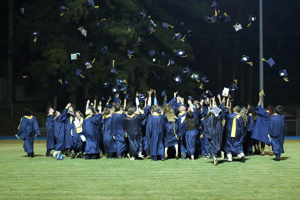 seniors throwing caps into air at conclusion of graduation