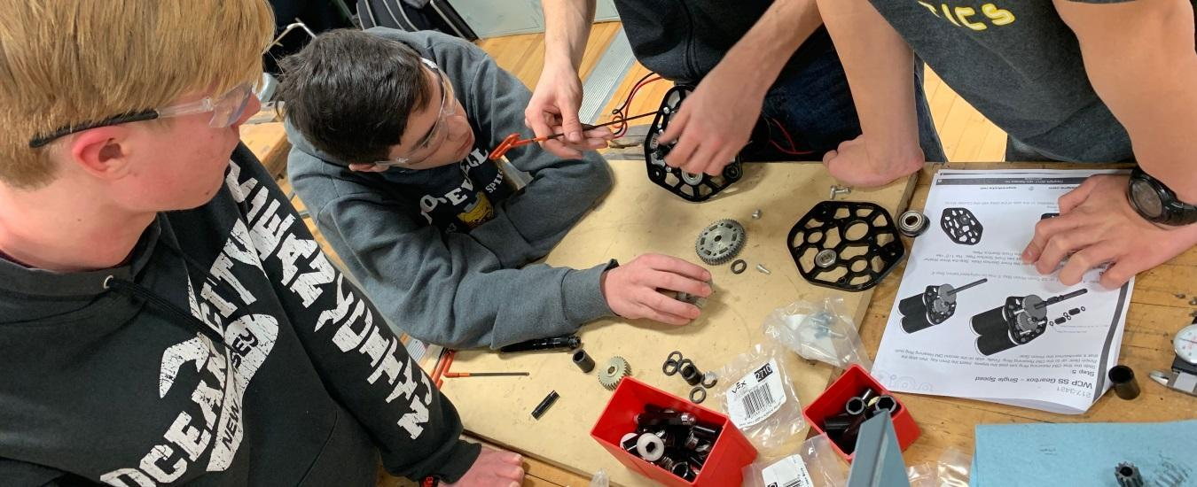 Central High Robotics team members construct a part for the competition robot.