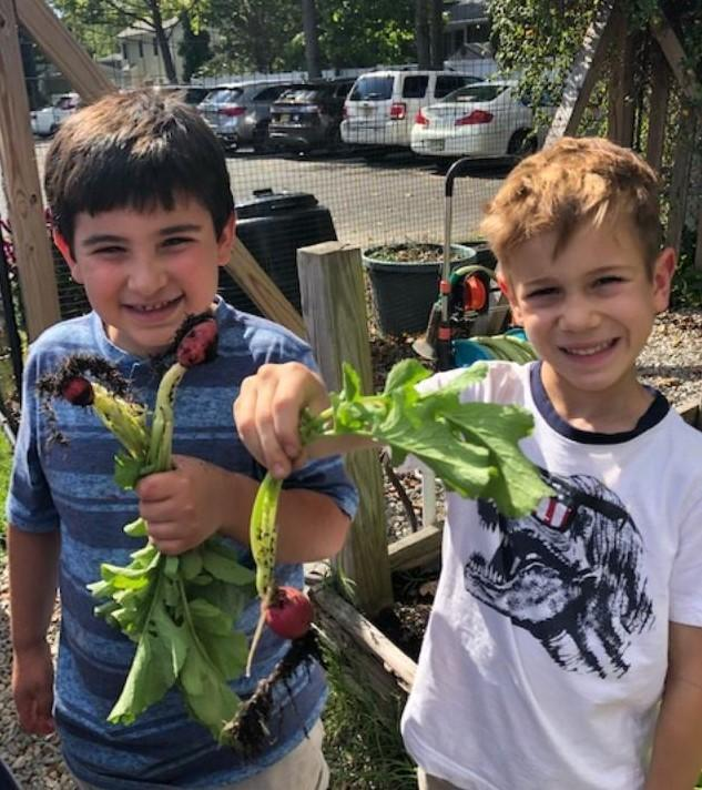 Photo of two Tamaques students harvesting fall bounty in Tamaques Garden.