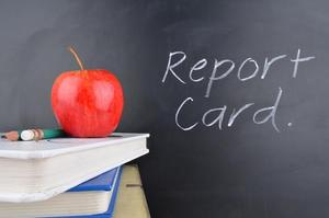 Picture of an apple on top of books with the words report card written on a chalkboard.