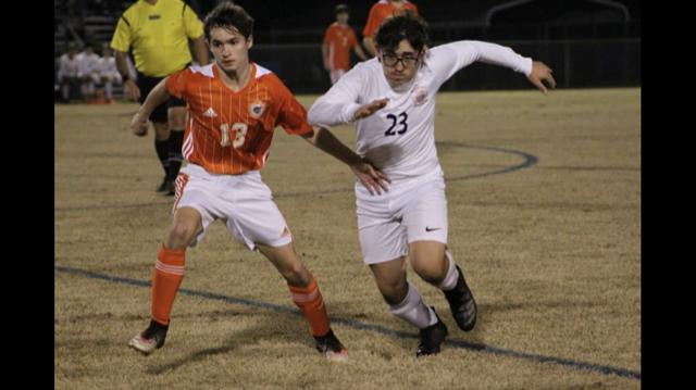 Bryson Noel kicking the soccer ball.