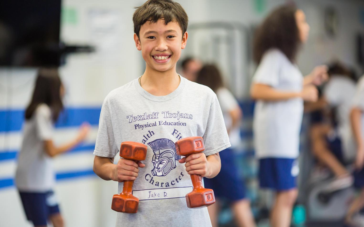 A young male student works out with free weights in the school gym.
