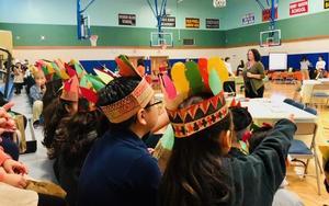 little boys and girls wearing their handmade feather head gear