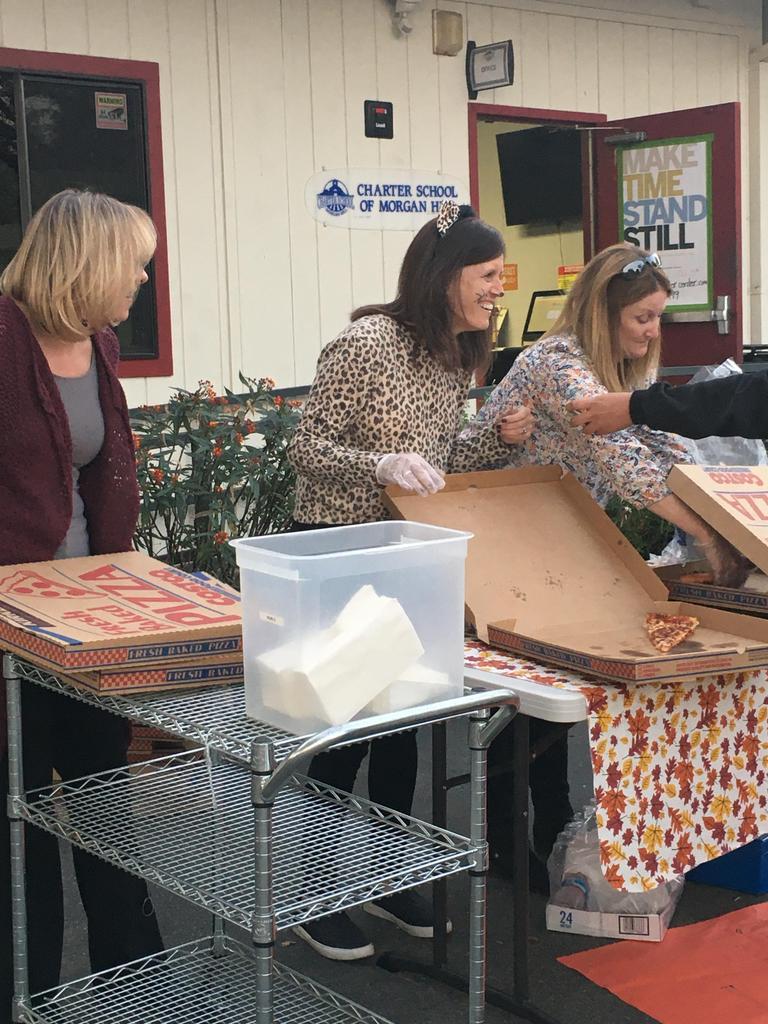 principal, executive director and teacher handing out pizza