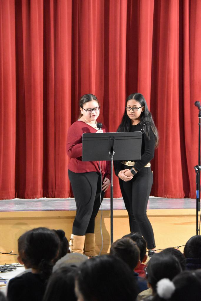 Two girls at a music stand, one who's holding a microphone