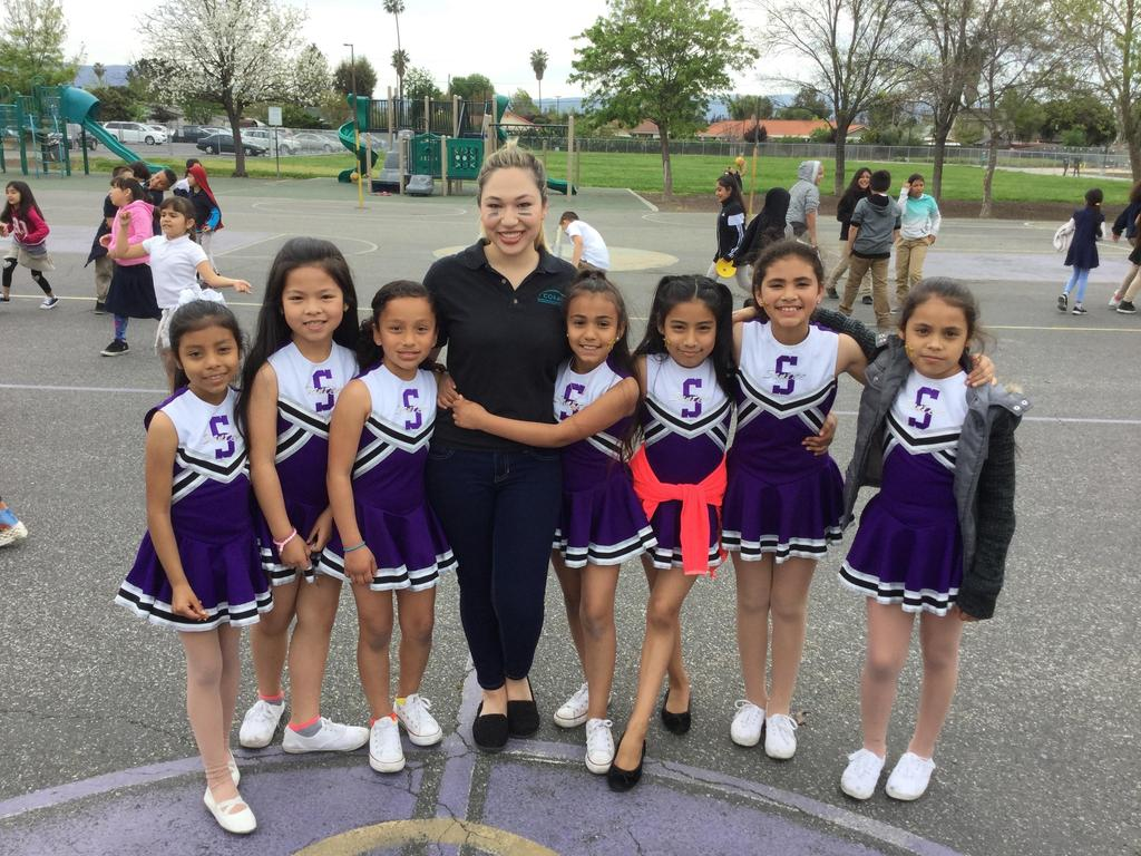 student cheerleaders pose with coach after dodgeball competition