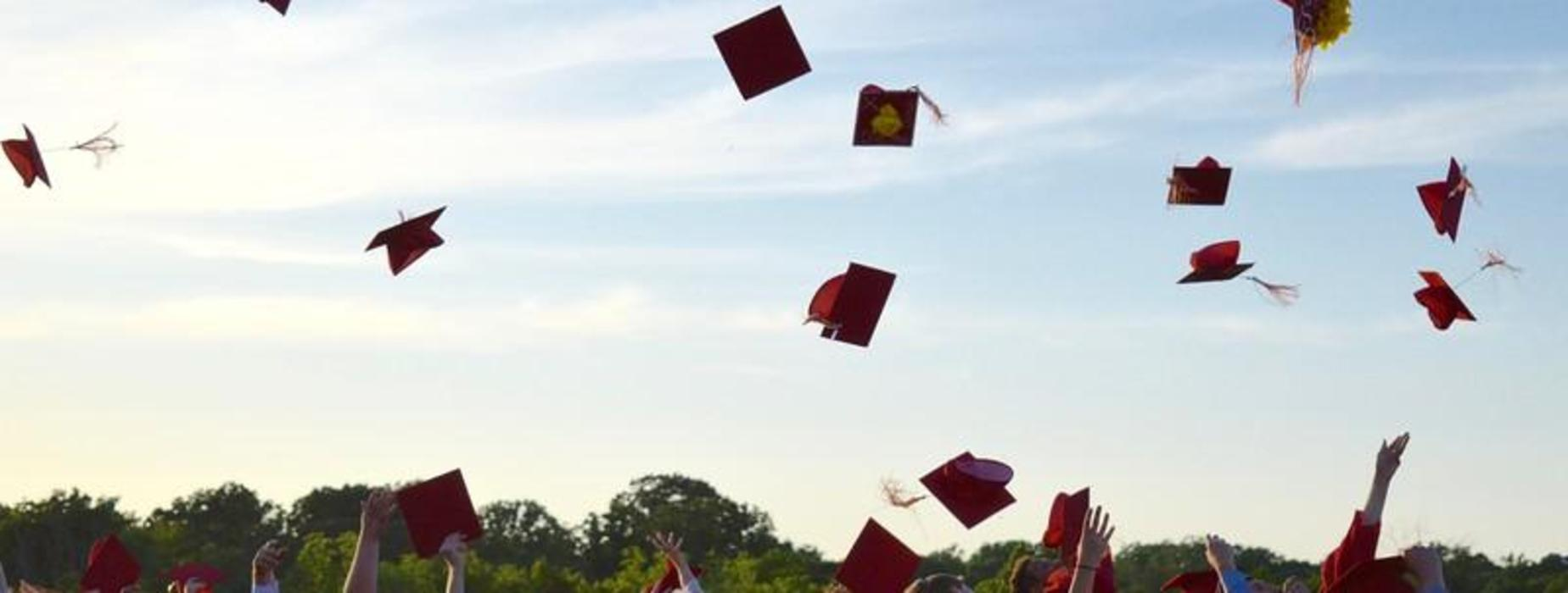 Graduation Caps flying in the air