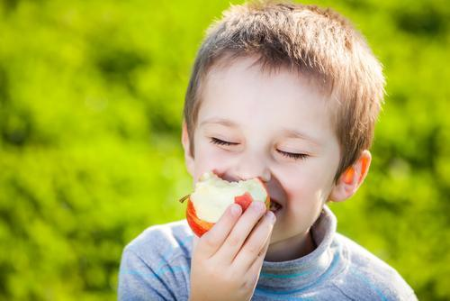 Younger boy taking a bite out of an apple.