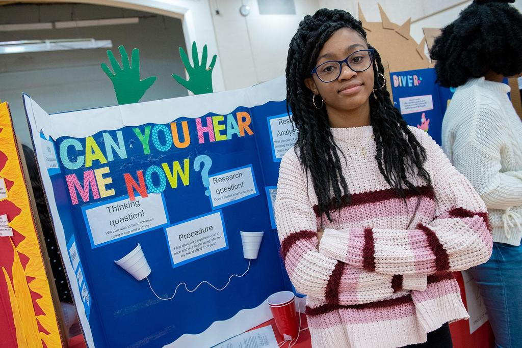 A student stands in front of her project called Can You Hear Me Now?