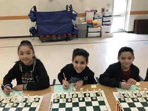 students posing together ready to play chess.