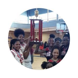 Female basketball players smiling while holding up trophy.