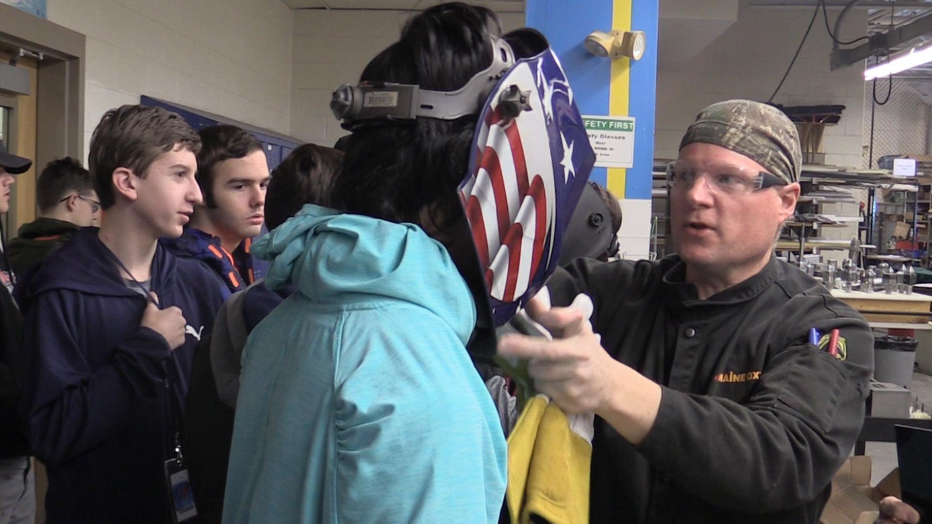 Mr. Burgher putting an American flag themed welding helmet on student
