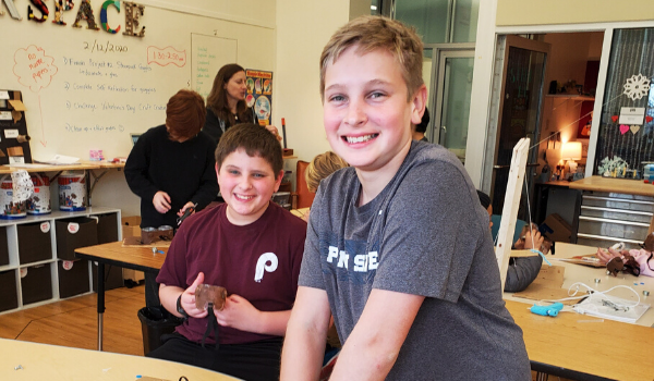 Two boys smiling in class.