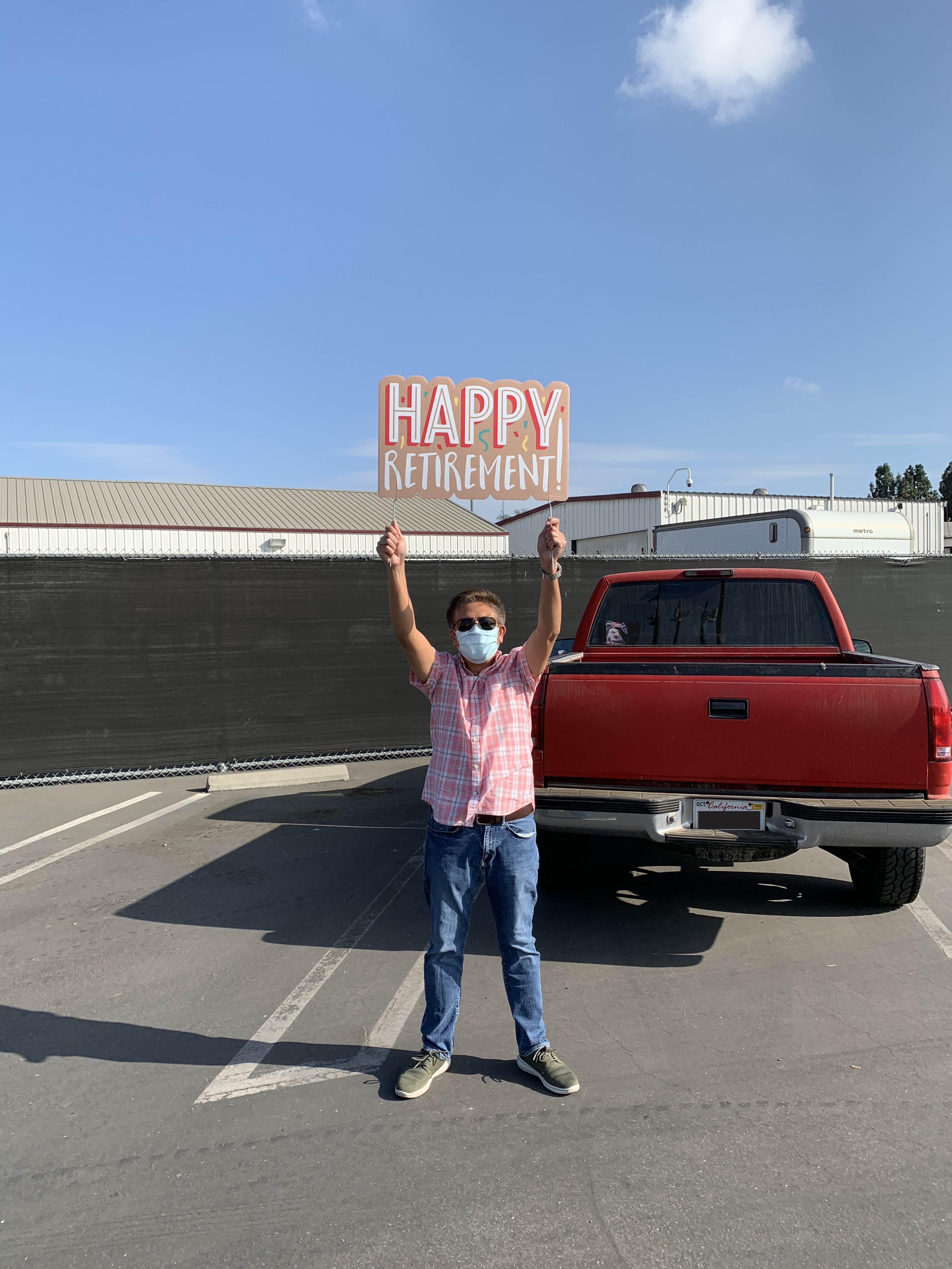 Staff member holding Happy Retirement Sign