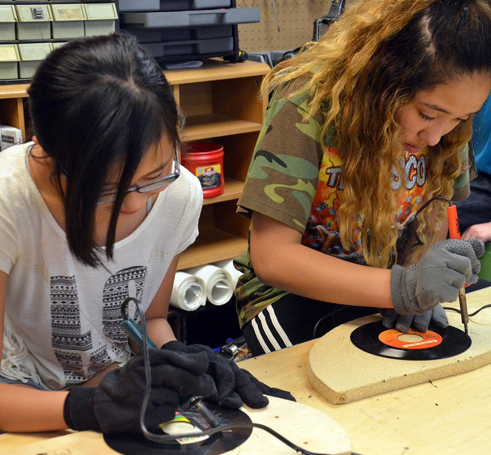 Middle school girls use soldering guns to create art out of old records