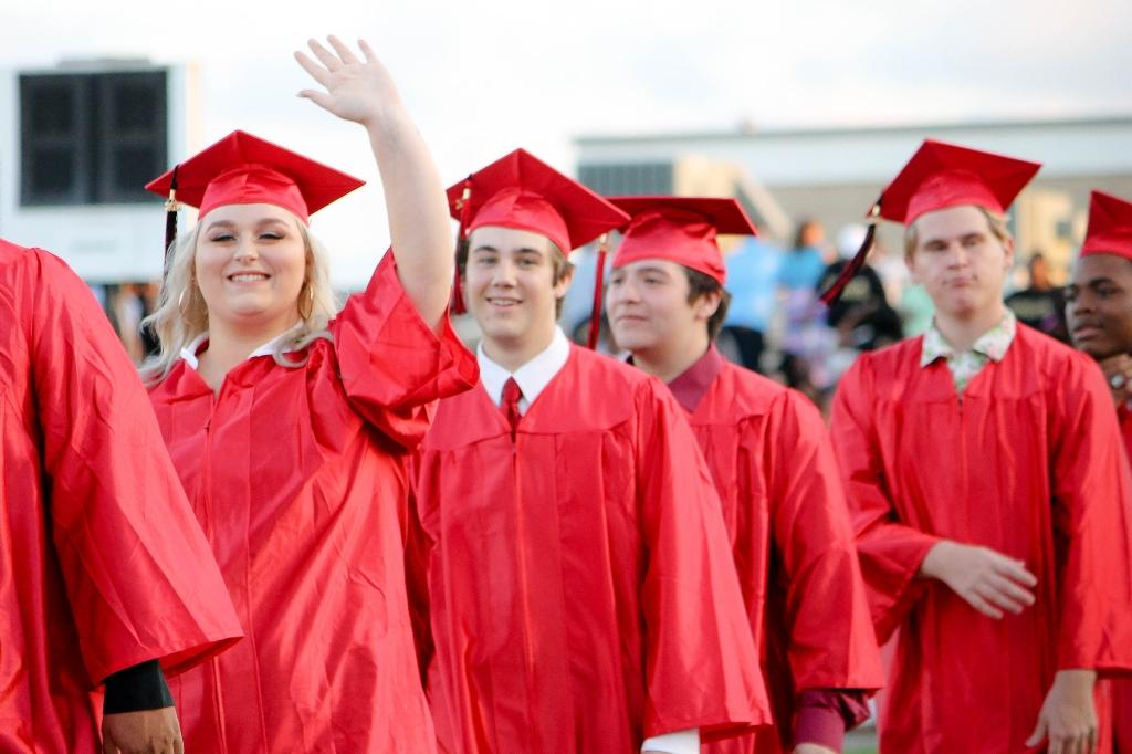 students of the victoria east high school 2018 graduating walking into memorial stadium, female student waiving to the crowd