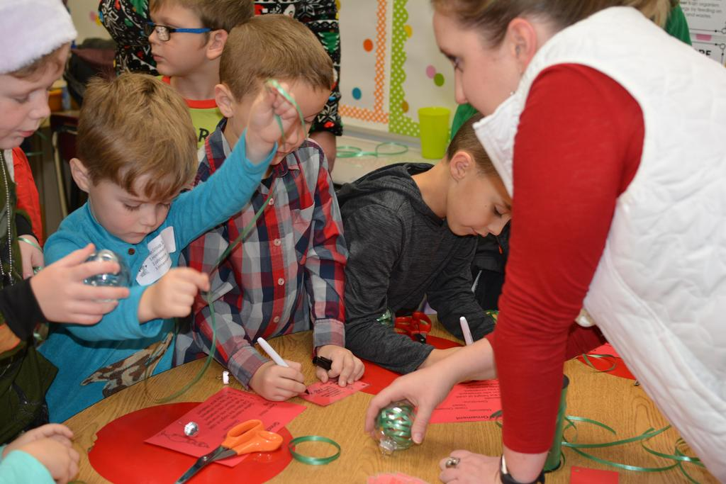 Ms. Sturgill helps students making Christmas ornaments on Grinch night