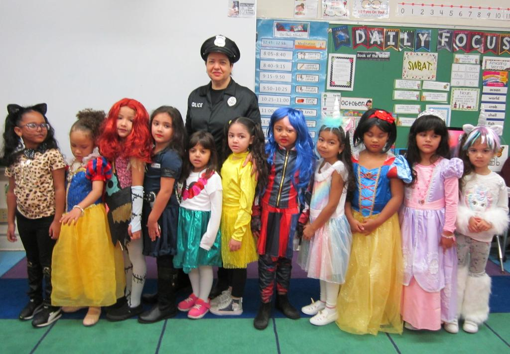 Mrs. Michaels dressed as a cop with the girls of her class in assorted costumes
