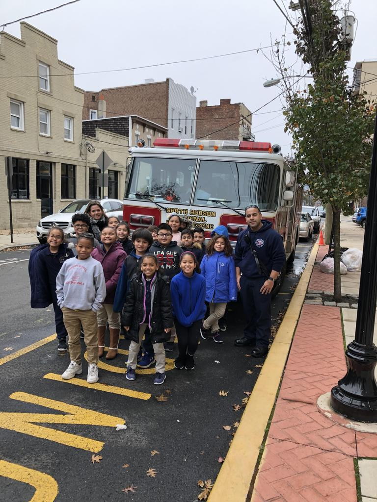 teacher and class with firefighter in front of the fire engine in front of the school