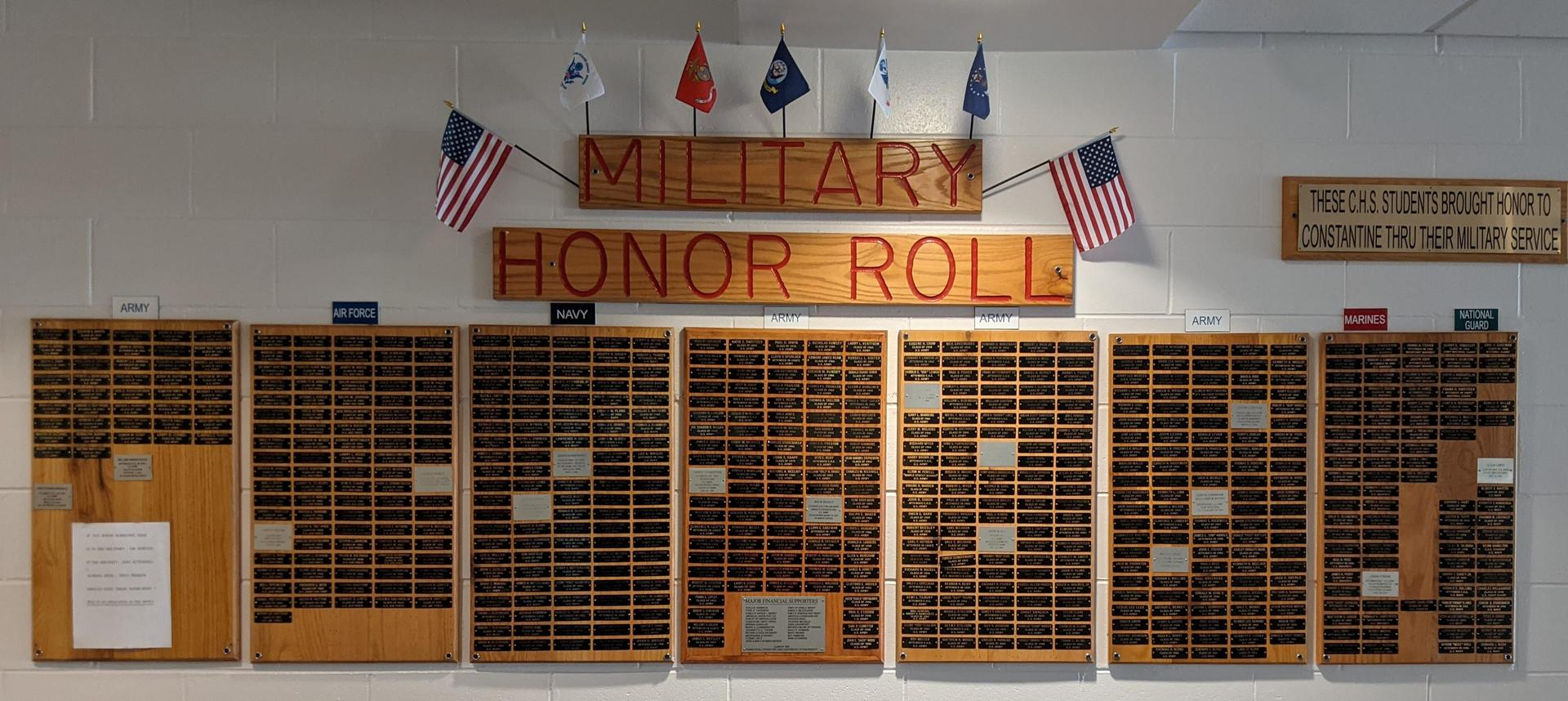 Photograph of the Wall of Fame that displays the flag and name of the various branches of the military and the names of C.H.S. students that enlisted in each.