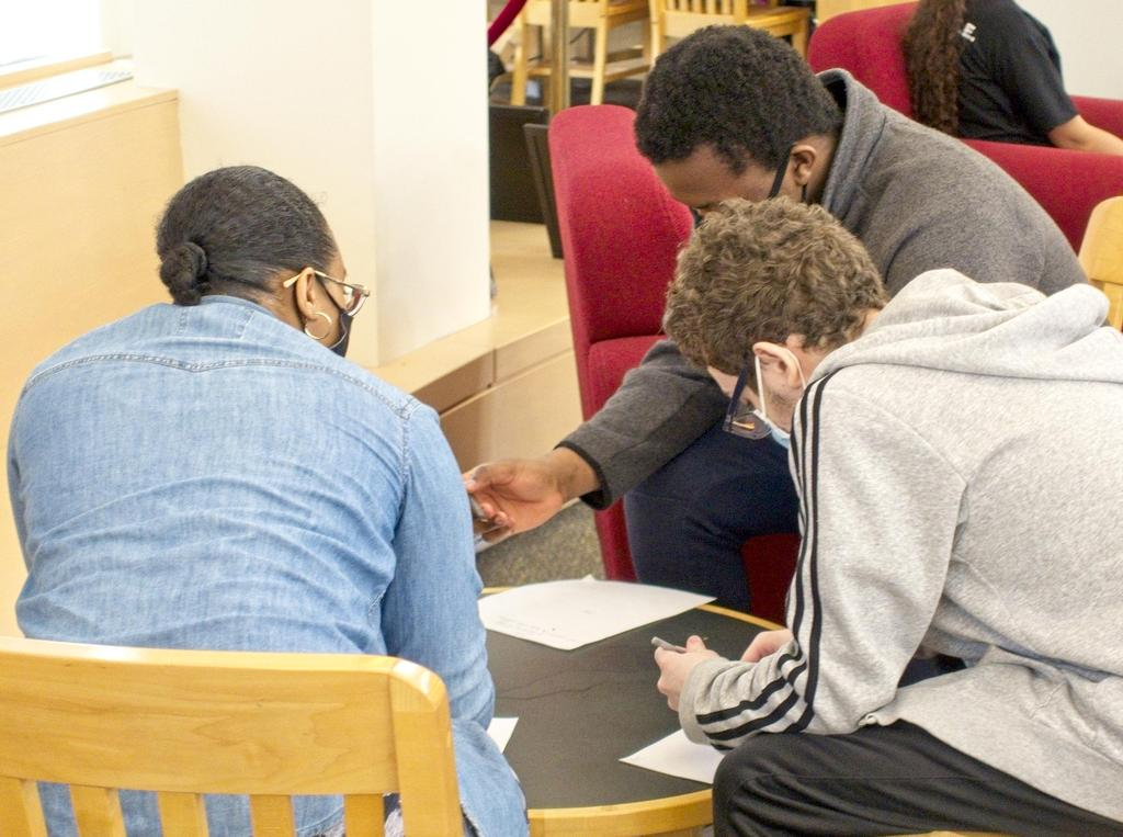 Three students working around a table