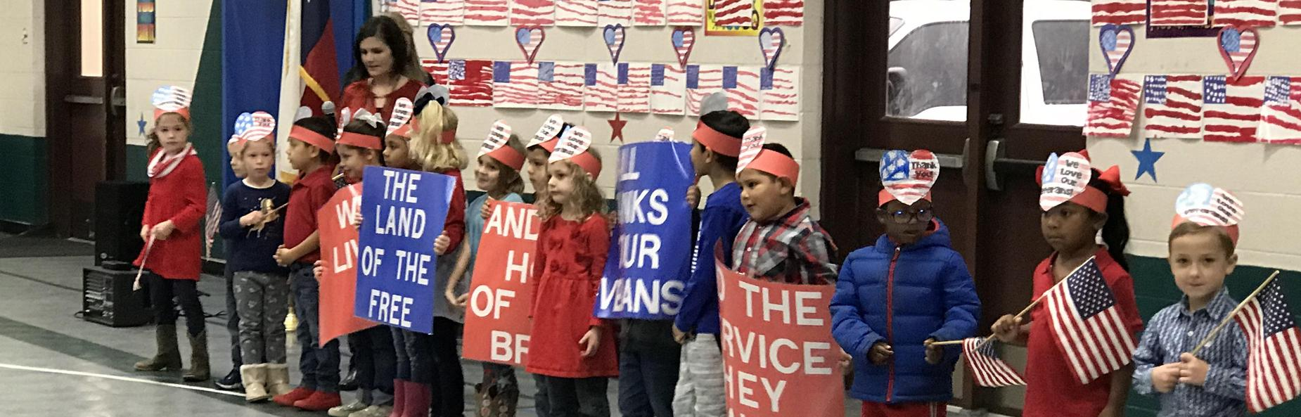 children holding american flags and patriotic signs