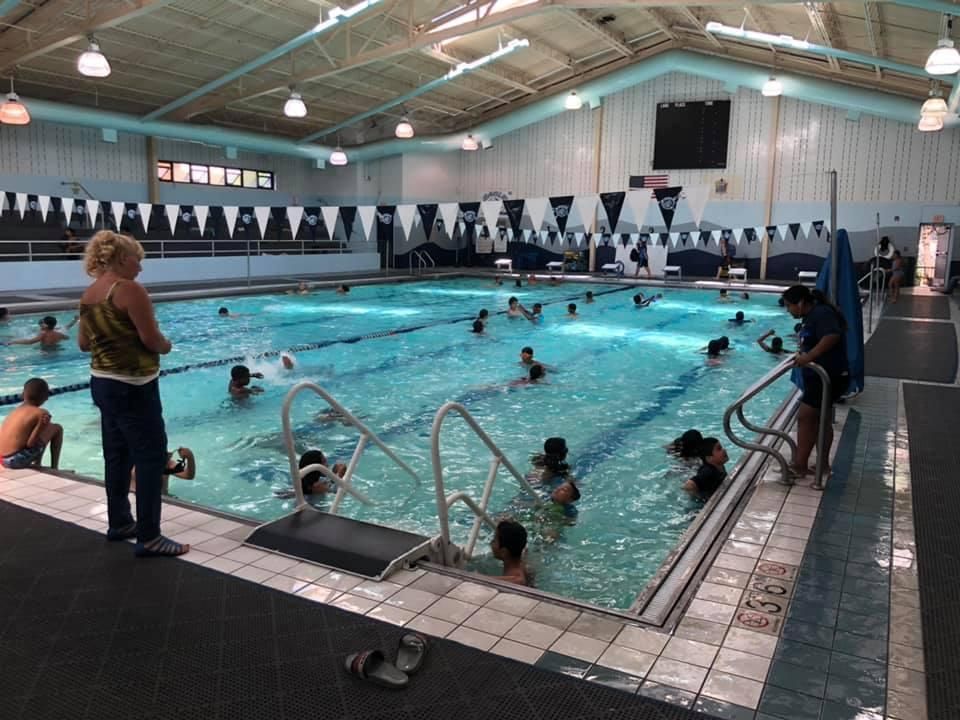 Students swimming in the indoor pool complex
