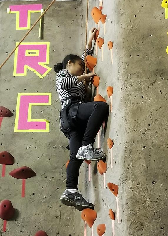 Young female student climbing the rock wall.