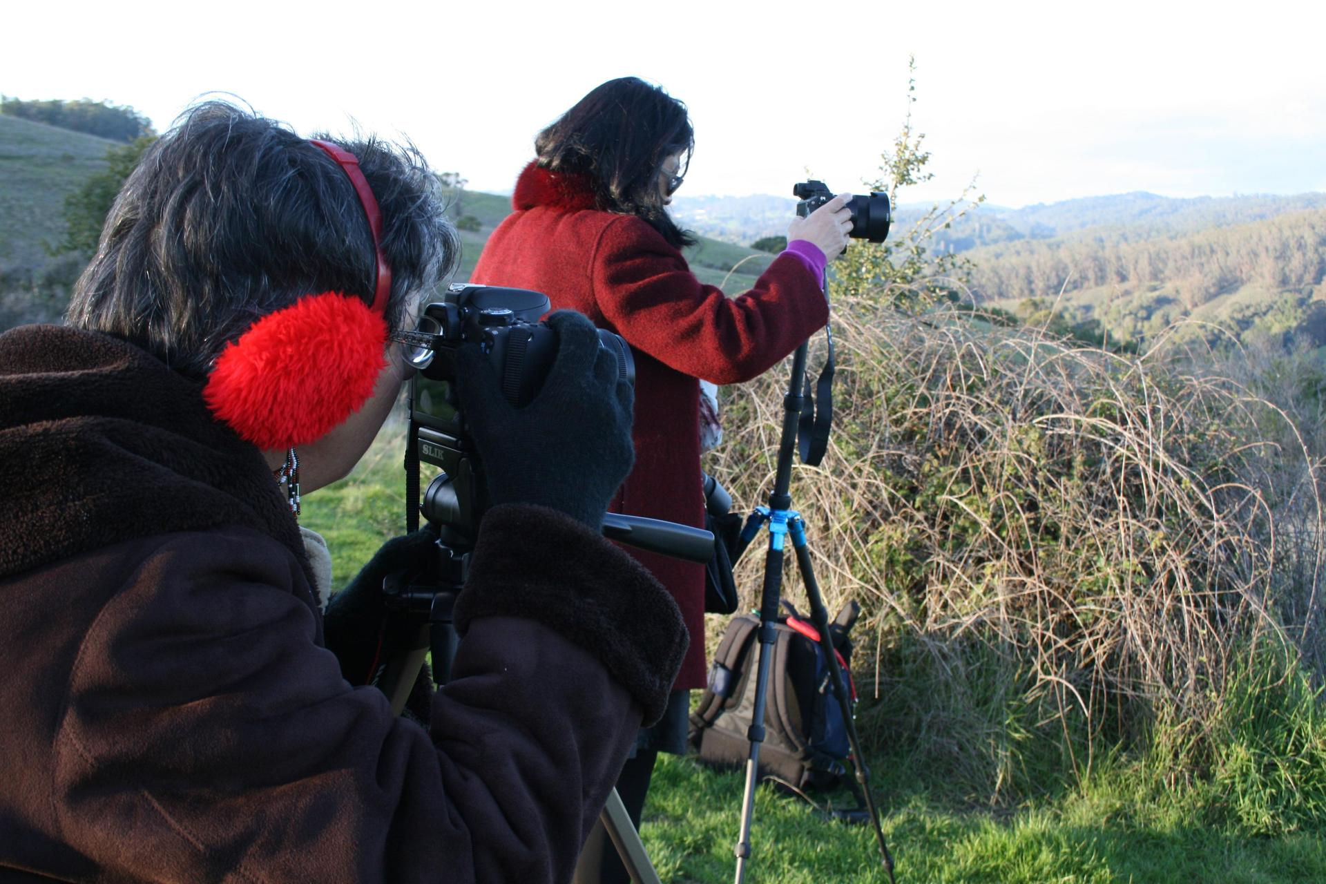 Two adult students look through camera viewfinders while standing on the ridge of a hill.