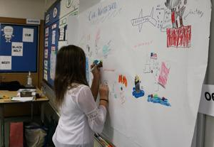 A Tamaques 5th grader helps to decorate a poster illustrating New Jersey's watershed, during a special visit by