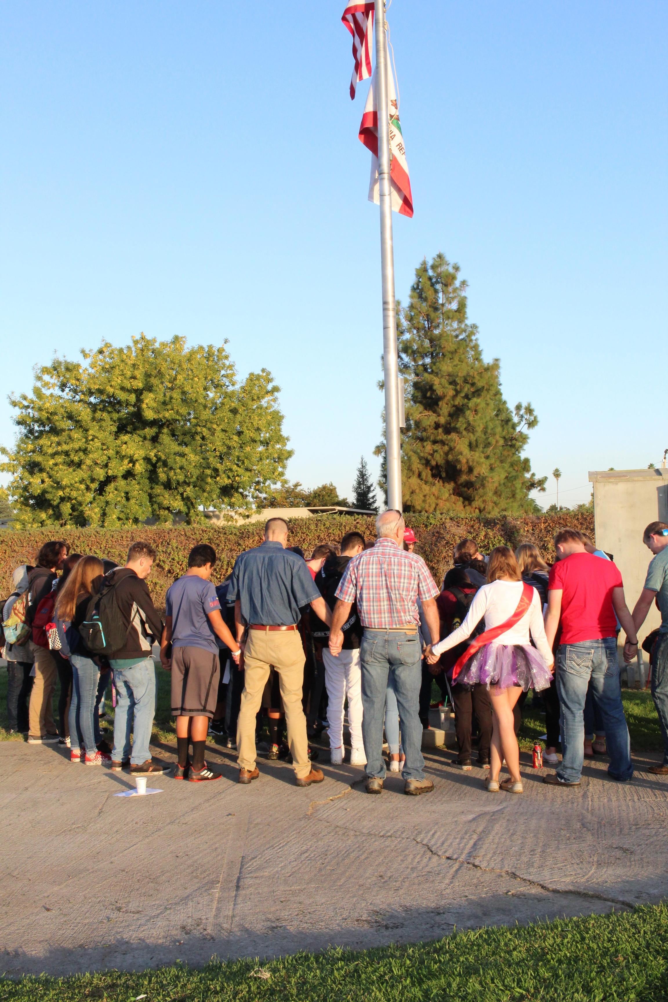 Students praying at the pole