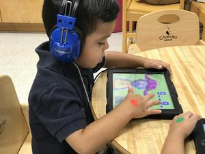 An Edinburg CISD prekindergarten student uses a tablet to complete his spelling and reading assignments..