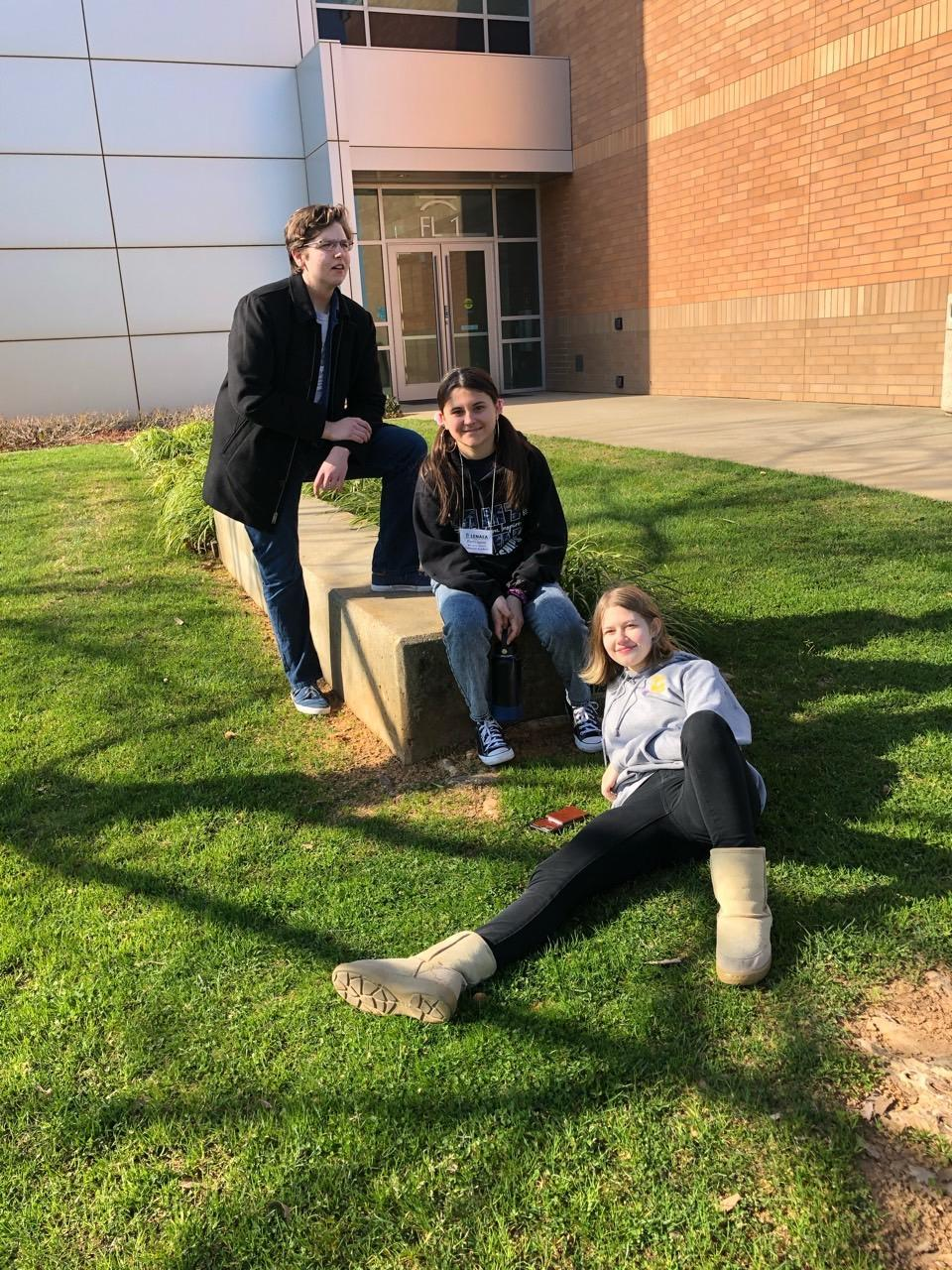 students leaning on school half wall