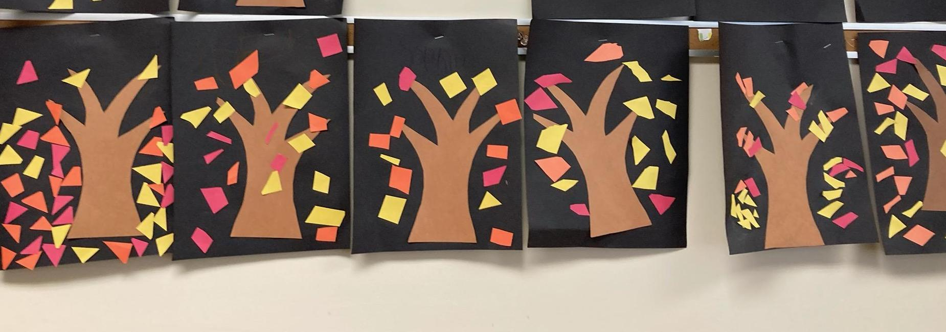Student created artwork of trees with red, orange, and yellow leaves falling