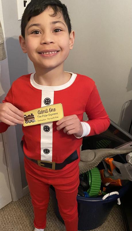 Rylon holding ticket in Santa pajamas
